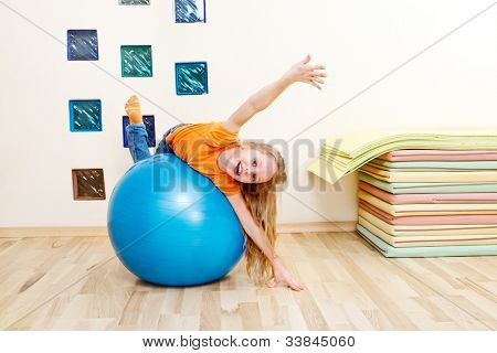 Laughing girl from a primary school lying on a large blue gymnastic ball