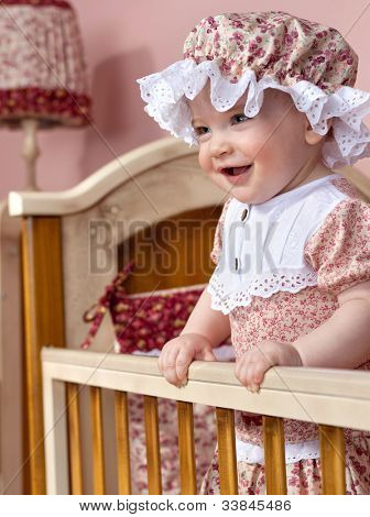 little child baby standing in bed smiling positive cheerful indoors babyroom
