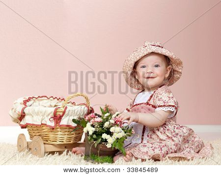 little child baby girl playing with flowers indoors in baby room on the floor on the carpet smiling happy