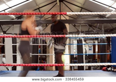 Action Shot Of Male Personal Trainer Sparring With Female Boxer In Gym Using Training Gloves