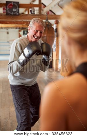 Senior Male Boxer Sparring With Younger Female Coach In Gym Using Training Gloves