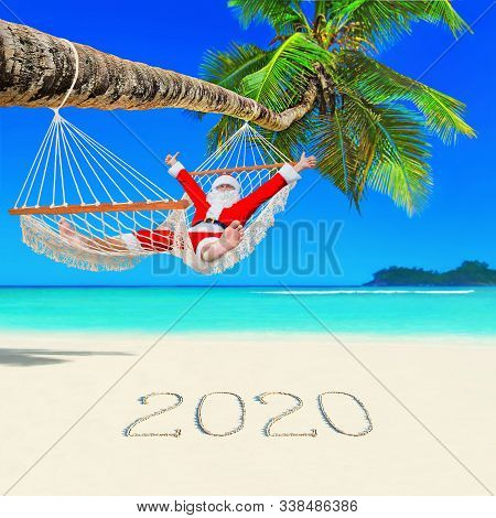 Santa Claus Thumbs Up Hands Positive Gesturing Relax In Mesh Hammock Under Coconut Palm Tree At Para