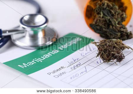 Close-up Of Marijuana Recipe Paper With Dry Trimmed Cannabis On Medical Table. Doctors Stethoscope T