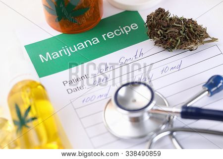 Close-up Of Doctors Table With Marijuana Recipe Paper. Plastic Bottle With Cannabinoid Oil And Dry H
