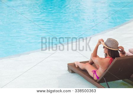 Young Woman In Swimsuit And Straw Hat Relaxing On Chaise-longue