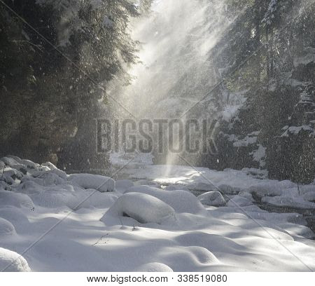 Mountain Alpine Canyon With Deep And Fast Flow. The Wind Drops Snow From Conifers Like Small Avalanc