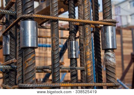 poster of Fittings interconnected by a nut at a construction site. The technology of splicing two metal rods.