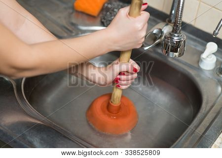 Female Hands Apply Plunger To The Kitchen Sink, No Face