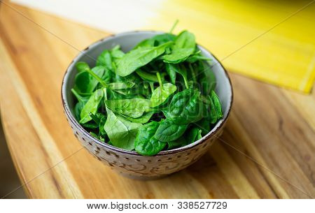 Fresh Spinach Leaves In A Bowl On A Wooden Table. Eco Vegan Spinach Salad