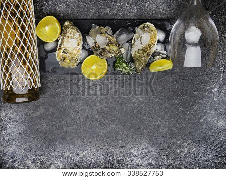 Oyster On Ice, Lemon Slices, Wine Bottle And Glass. Delicatessen And Gourment Food, Rich In Iodine,