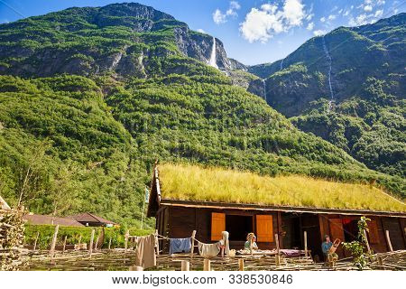 Gudvangen, Norway - June 13 - Traditional Wooden House And People In National Clothes In The Viking