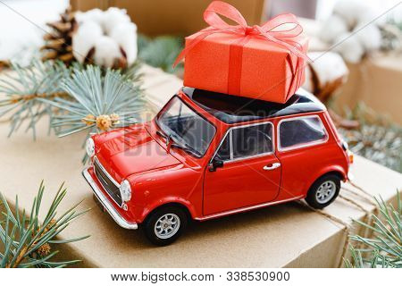 Red Toy Car With A Christmas Red Gift Box On The Roof. Christmas Background With Cotton, Fir Branche