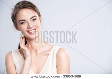 Portrait of a smiling young woman with a brown hair. Beautiful  young female model with healthy skin of face - isolated on white background. Young attractive  girl looking to the camera