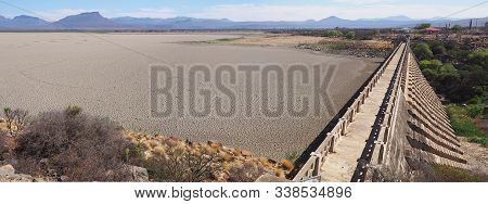 View Over Parched And Empty Dam, With Cracked Mud