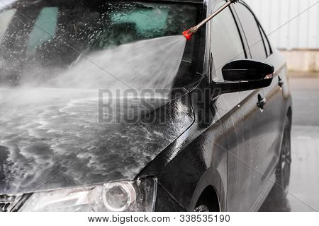 Car Wash Equipment. A Man Is Washing A Car At Self Service Car Wash. High Pressure Vehicle Washer Ma
