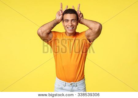 Cute Masculine And Silly Hispanic Boyfriend In Orange T-shirt, Make Peace Gesture, Bunny Ears Behind