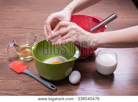 Woman Breaking Egg In A Bowl To Cook A Homemade Cake Made From Scratch