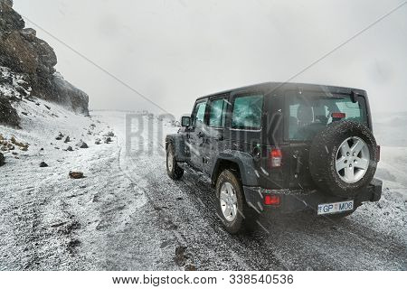 VIK, ICELAND - MAY 03, 2018: Jeep Wrangler Unlimited four wheel drive vehicle on a mountain road with snow