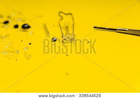 Splinters From The Broken Glass Light Bulb Isolated On Yellow Background