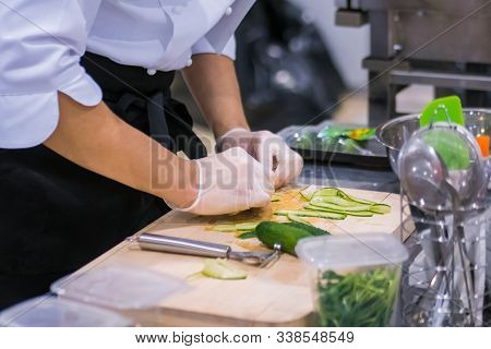 Chef Hands Peels And Slices Fresh Green Cucumber, Pickle With Scraper, Knife At Cuisine Of Restauran
