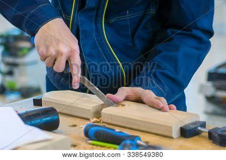 Professional Man Carpenter Using Chisel To Carve Wood On Rough Workbench At Workshop. Design, Carpen