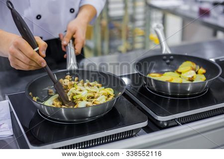 Chef Cooking Sliced Champignon Mushrooms, Onions And Potatoes In Frying Pans With Oil On Electric St