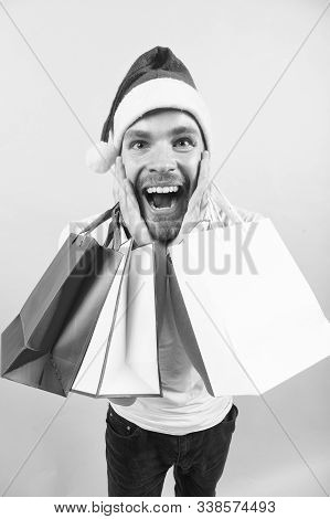 Macho Shopper With Surprised Face Hold Paperbags. Man In Santa Hat With Bags On Orange Background. C