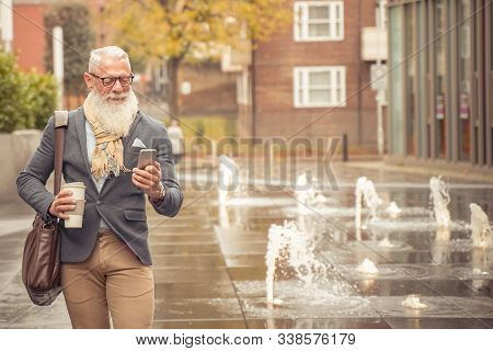 Happy Senior Businessman Looking Cellular Phone And Drinking A Hot Coffee After Of The  Work. Man Wa