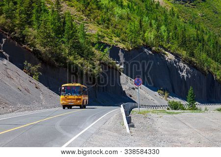 Altai, Russia - 07.12.2019: A Large Yellow School Bus With The Words Children In Russian Rides On A