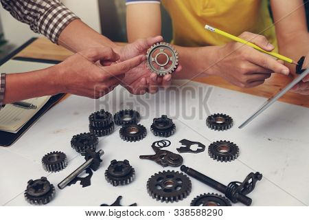 Engineer Discussing And Designing About Mechanical Gear Parts In Office.