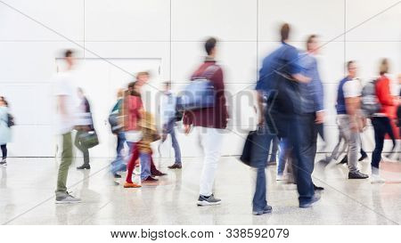 Large anonymous blurred crowd goes to trade fair or congress