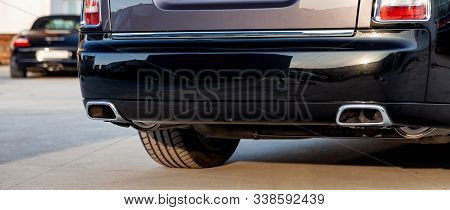 Close-up Of A Black Luxury Car Bumper Of An Sedan With Two Side Turbo Exhaust Pipes Outdoors On Asph