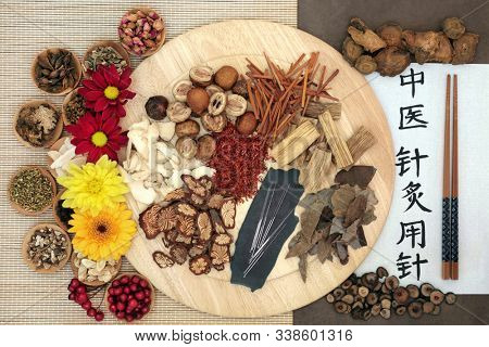 Chinese herb selection & acupuncture needles with calligraphy script. Translation reads as acupuncture needles used in traditional chinese medicine. Flat lay, top view. Natural health care concept.