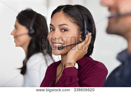 Smiling beautiful woman working in call center as telemarketing operator. Customer support agent wearing headset at office, while looking at camera. Middle eastern girl working as telephone operator.