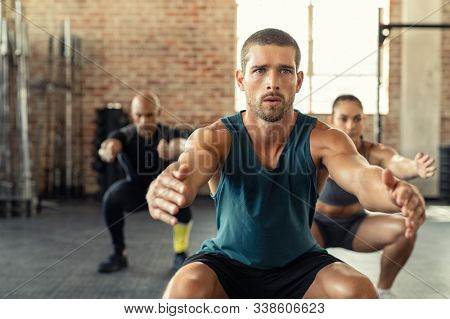 Young man exercising with squat in gym with people in background. Fit man exercising with stretched hands and squats at gym. Fitness class squatting togeher with outstretched during an exercise.