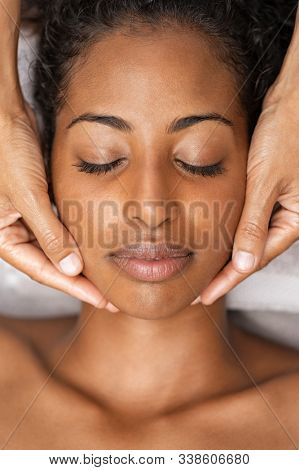 African american woman at spa getting face massage. Beautiful young woman getting head massage in spa wellness center. Close up face of black girl with closed eyes relaxing during beauty treatment.