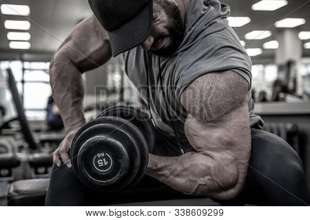 Strong Young Bearded Man In Cap Lifting Heavy Weight Dumbbell On Muscle Biceps Sitting With Great Ef