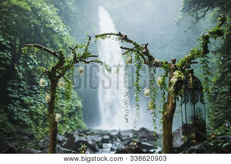 Wedding Ceremony On Huge Waterfall Nung Nung In Bali, Indonesia Jungle. Arch With Dry Wooden Branche