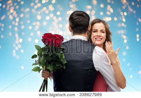 love, couple, proposal and people concept - happy woman with engagement ring and bunch of roses hugging man over holiday lights on blue background