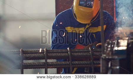 Welding Fittings With Electrodes. Welder In Mittens And Helmet With Electrode Holder. Electrode Weld