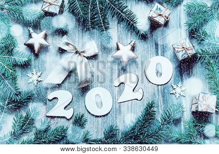 New Year 2020 background with 2020 figures, Christmas toys, blue fir tree branches and snowflakes. New Year 2020 festive holiday still life