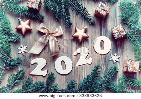 New Year 2020 background with 2020 figures, Christmas toys, green fir tree branches on the wooden background. New Year 2020 festive still life