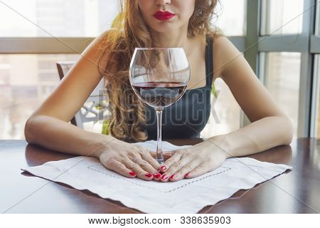 Young Woman Sitting Alone At Desk With Glass Of Wine. Beautiful Gorgeous Girl Drinking Alcohol In A