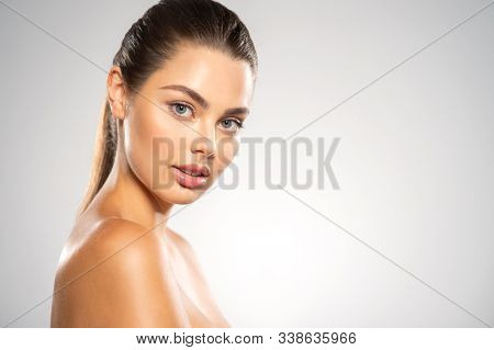 Close-up face of beautiful woman looks to the camera. Young   model with  health fresh face - isolated on white background. Young caucasian  girl with a fresh clean skin fa a face.