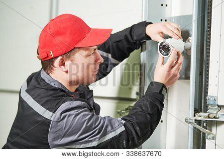 video surveillance service. Technician installing camera