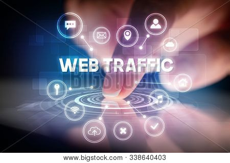 Finger touching tablet with web technology icons and WEB TRAFFIC inscription, web technology concept