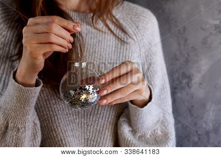 Woman Holding Christmas Glass Ball With Glistening Star Pailettes Inside, Holiday Concept