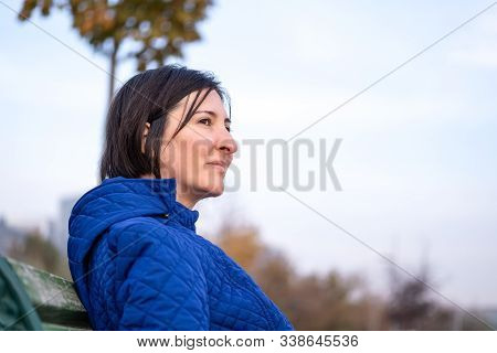 Young Beautiful Woman Wearing Blue Coat Sitting On Bench In Park. Nature Environment Background.