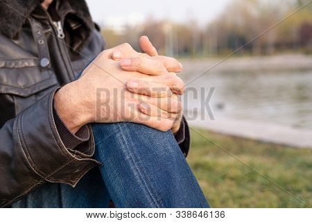Close Up Hands Of A Caucasian Man Wearing Brown Leather Jacket Sitting And Resting On Grass Near Pon
