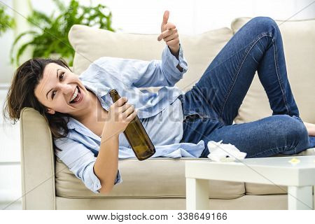 Drunk Woman Is Laying On The Sofa, Holding An Empty Bottle. She Is Smiling Crazingly. Close Up.